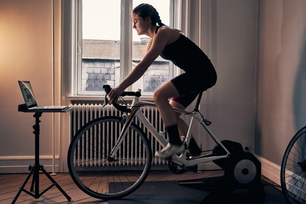 Female cyclist riding on a turbo trainer