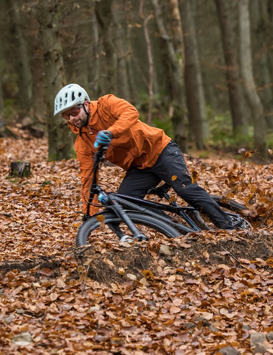 Male cyclist riding the hardtail Kinesis Rise Pro eMTB through woodland