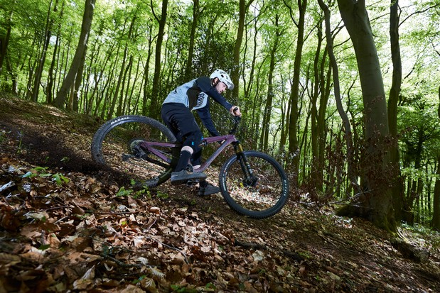 Male cyclist in blue top riding the Nukeproof Reactor ST full suspension mountain bike