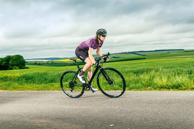Female cyclist riding a Planet X London Road through the countryside