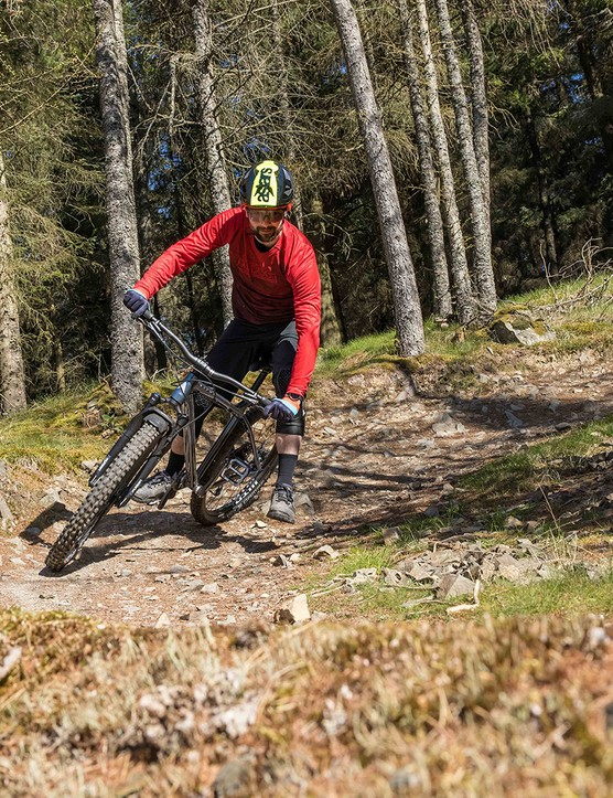 Male cyclist in red top riding the Vitus Sentier 27 hardtail mountain bike over rough ground