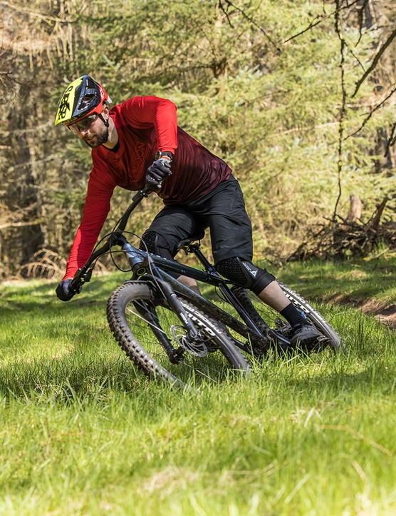 Male cyclist in red top riding the Vitus Sentier 27 hardtail mountain bike through woodland