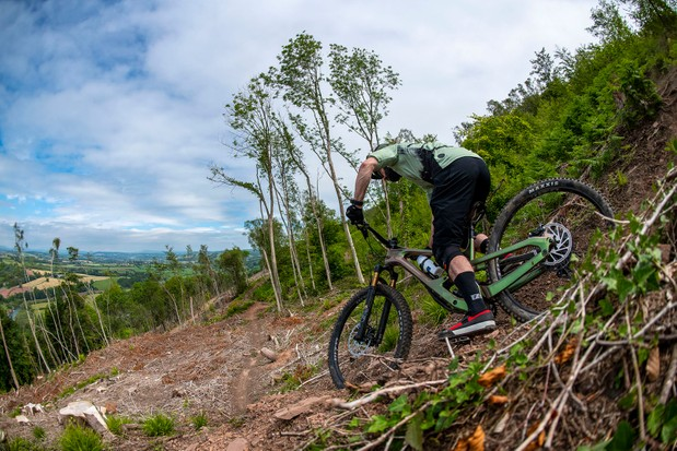 Male cyclist riding the Cannondale Jekyll through woodland