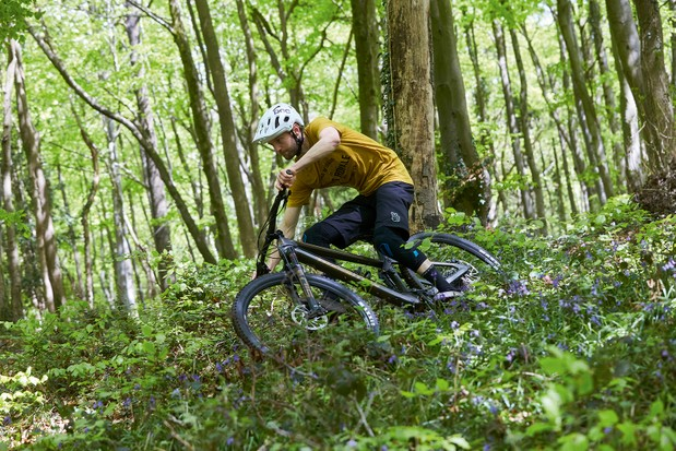Cyclist riding the Transition Spur X01 Carbon full suspension mountain bike through woodland