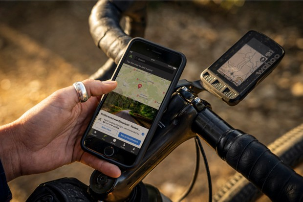 Picture showing cyclist use Komoot on a phone with a Wahoo in the background