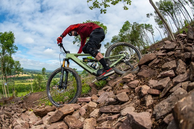 Male cyclist in red riding the Nukeproof Megawatt 297 Full Suspension mountain ebike downhill over rocks