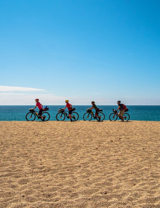Sophie Gordon (Cycling UK), Katherine Moore (Unpaved podcast), Vedangi Kulkarni and Rob Penn (freelance journalists) push their bikes across the deep sand of the Loe Bar. The sand bar separates the Loe lagoon from the sea, and is one of several route options and shortcuts on the West Kernow Way.