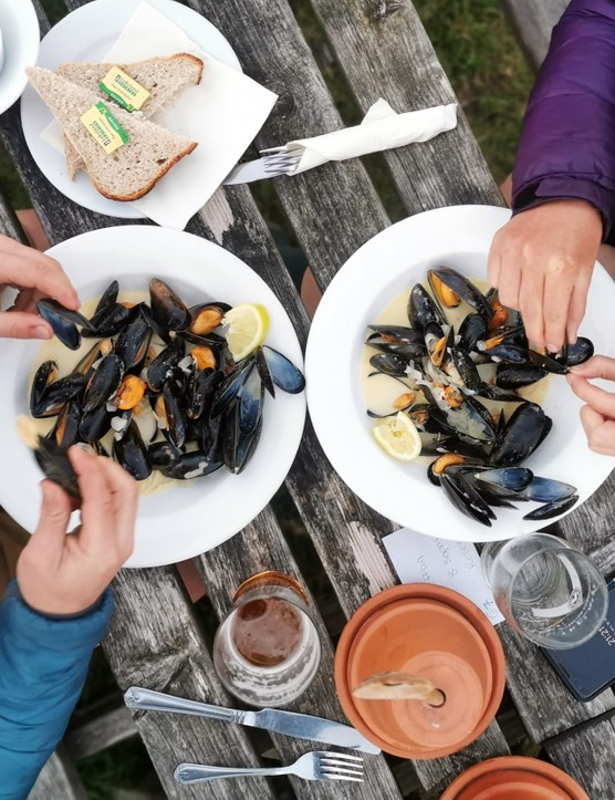 Sam Jones (Cycling UK) and Katherine Moore (Unpaved podcast) tuck into freshly caught mussels in Coverack after a day riding Cycling UK's West Kernow Way, June 2021. The 230km route is part of the EU-funded EXPERIENCE project to develop sustainable year-round tourism activities in Cornwall.