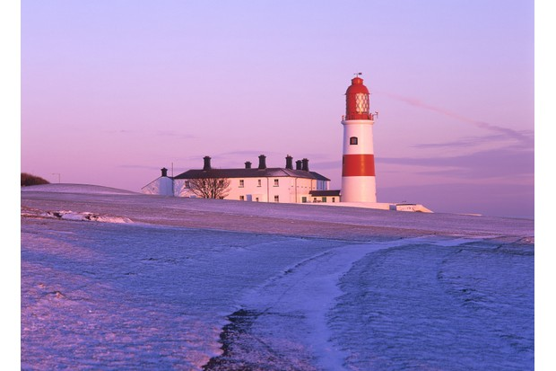Lighthouse at sunset in the snow