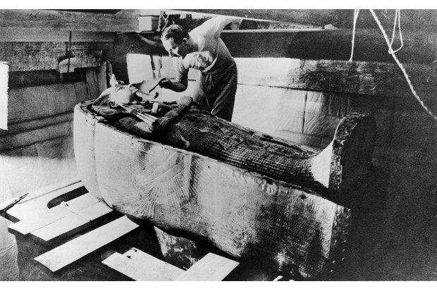 Archaeologist Howard Carter opening the coffin of Tutankhamun, 1922