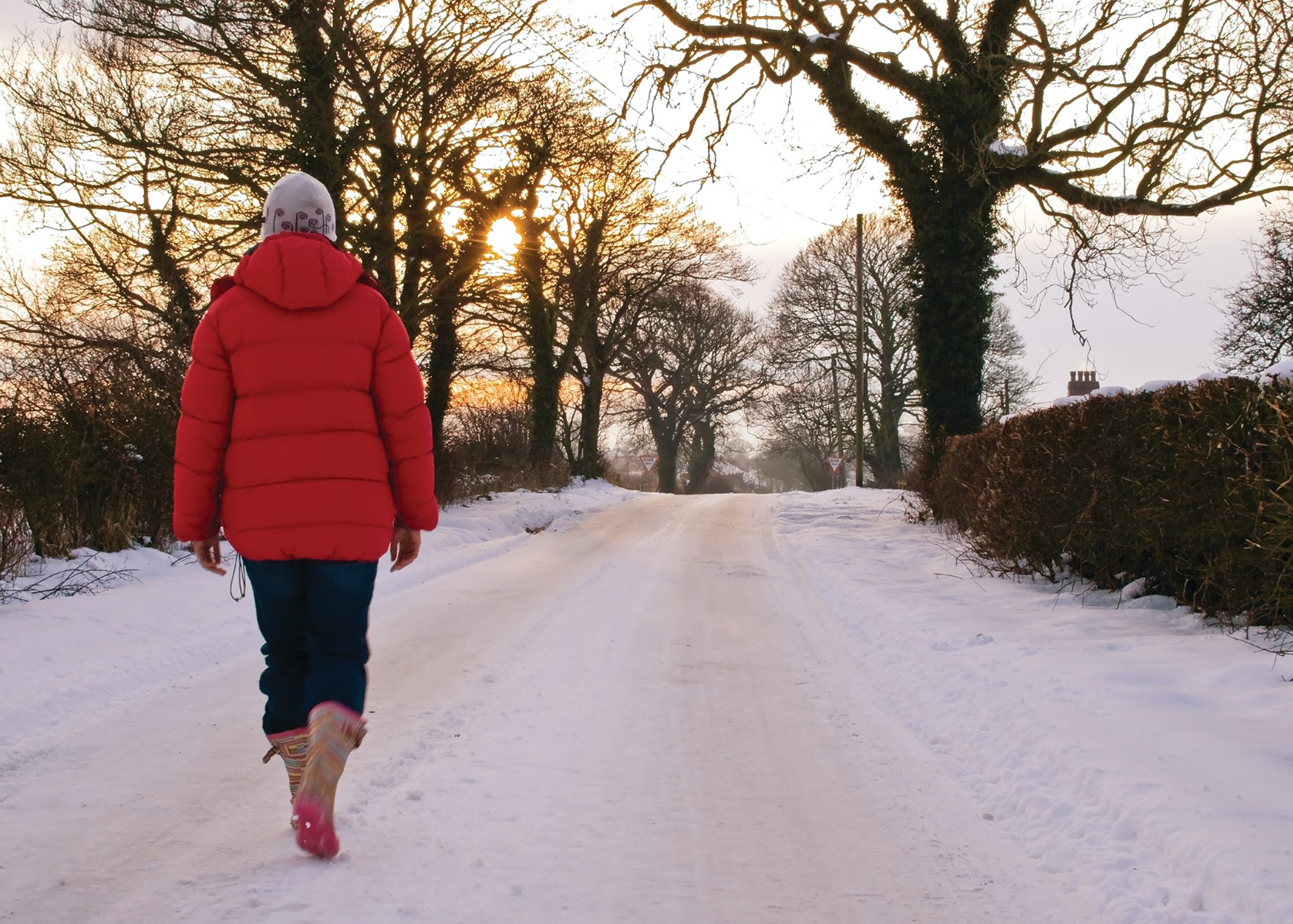 Woman walking in snow wearing down jacket