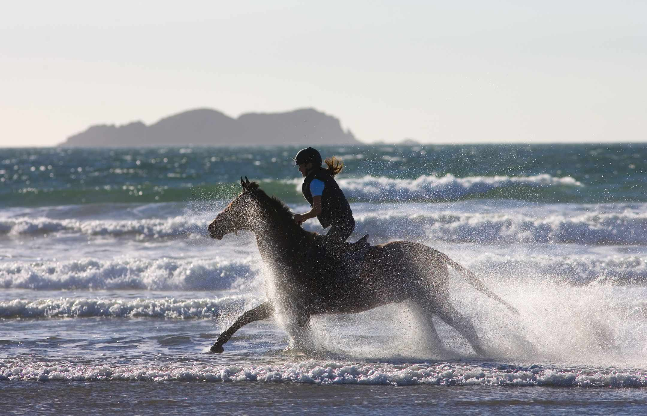 Horse riding on beach, Wales, UK