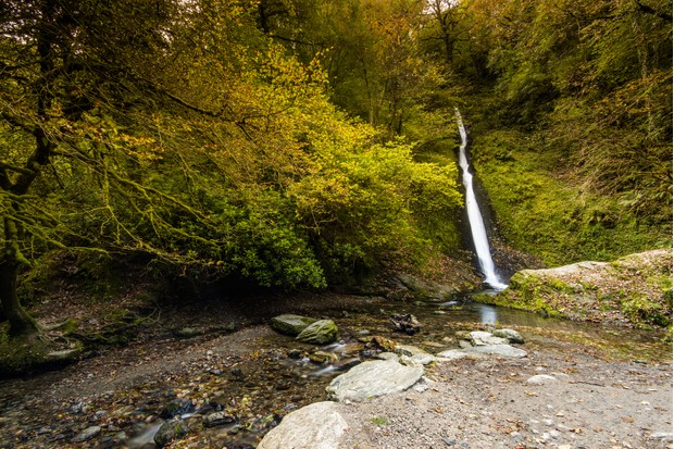 Wild scenic waterfall in autumn forest