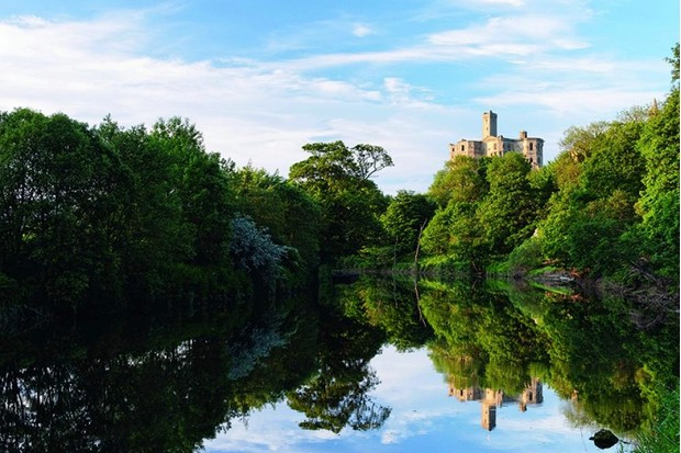 The cross-shaped keep of medieval Warkworth Castle rises high above the Coquet