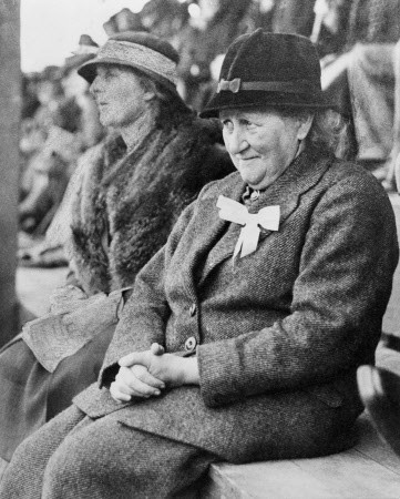 Beatrix Potter sitting outdoors on bench, wearing tweed suit and hat, at Keswick Show -of which she was President, September 1935. Ref. HIL R222. Original photographer unknown - work may be in copyright