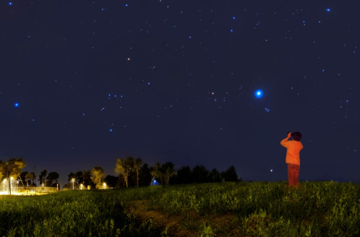 Kid looking at the stars with binoculars