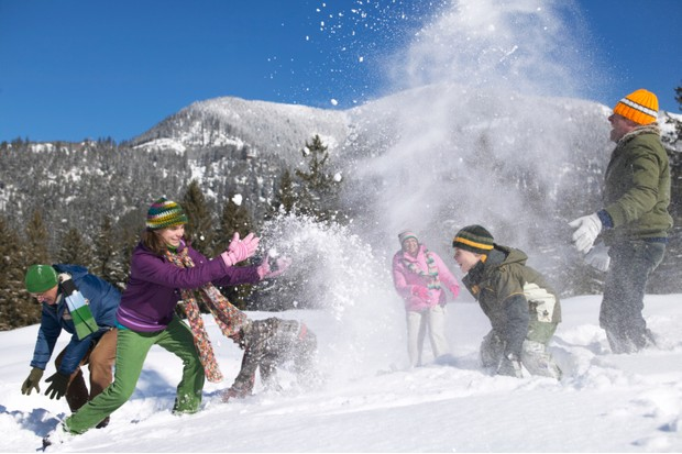 Three generational family having snow ball fight, in alpine landscape