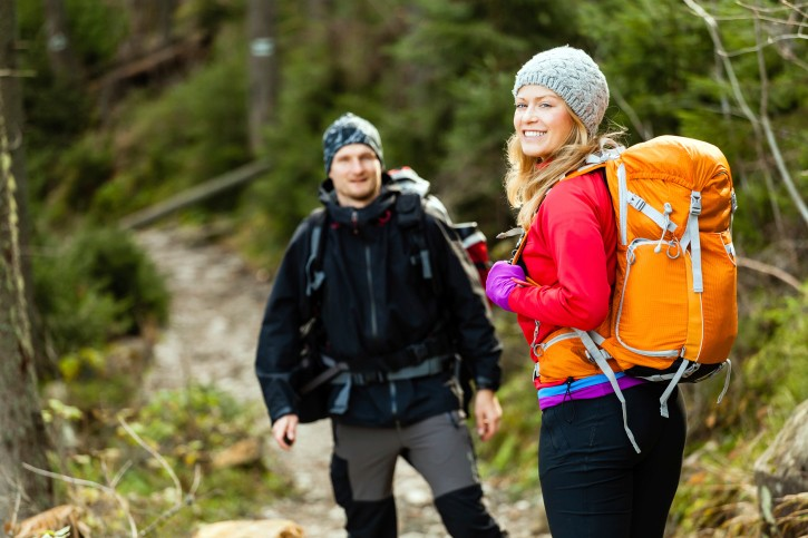 Couple happy hikers walking in forest