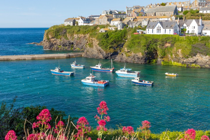 Boats turquoise sea and harbour walls Port Isaac Cornwall England