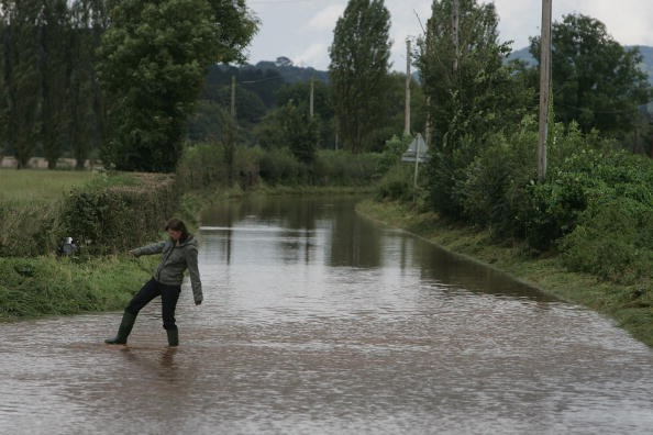 WORCESTER, UNITED KINGDOM - SEPTEMBER 06:  A woman makes her through a flooded road near Tenbury Wells on September 6 2008 in Worcestershire, England. Heavy rain has caused flash floods and flooding leading to widespread disruption to many parts of the UK.  (Photo by Matt Cardy/Getty Images)
