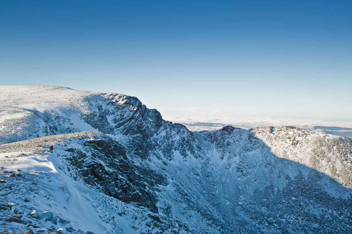 A-mountaineer-at-the-top-of-the-cliffs-of-Coire-an-t-Sneachda-with-Cairn-Lochan-in-the-background_2-b08c049