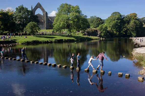 Families risk falling in the River Wharfedale while walking over the stepping stones at Augustinian Bolton Priory, North Yorkshire. Carefully stepping stone by stone, a young girl holds the hand of an adult who guides her across to the other side. The monastery was founded in 1154 by the Augustinian order, on the banks of the River Wharfe. The land at Bolton, as well as other resources, were given to the order by Lady Alice de Romille of Skipton Castle in 1154. It is now a popular loaction for families and walkers who can trek the River Wharfe upstream into ancient woodland.