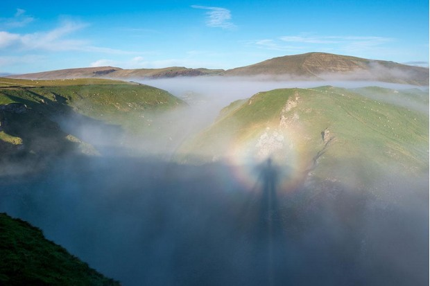 Spectacular misty landscape of Winnats Pass and Mam Tor in Derbyshire. Morning sunlight creating the natural phenomena of a Brocken Spectre. The shadow of the photographer surrounded by a halo in the mist. Credit: R A Kearton/Getty