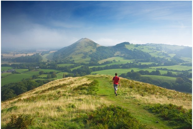 Caucasian male walker (30 years old) on Caer Caradoc heading for The Lawley. Shropshire. England. UK.
