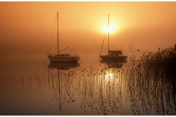 Sunrise on a misty morning with yachts on the Coniston Water, near Blawith in the Lake District