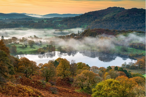 Loughrigg tarn misty autumn morning near Ambleside and Windermere. Lake District, Cumbria. UK,