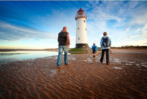 Family (parents and young son walking at sunset Wales Coast Path Talacre Lighthouse Near Point of Ayr Flintshire North Activities and Sports