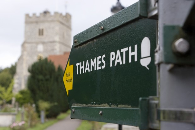 Sign pointing to the Thames Path with Holy Trinity church (not National Trust) in the distance, at Cookham, Berkshire.