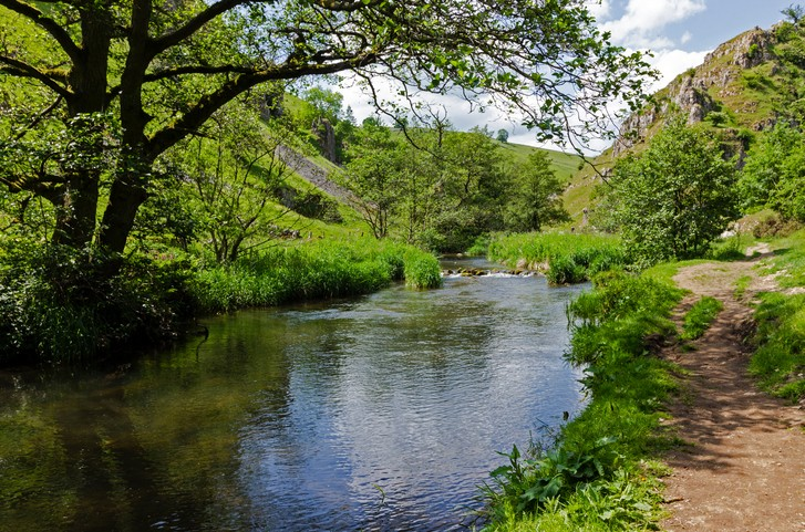 The river Dove runs parallel to a footpath in a junction between Biggin Dale and Wolfscote Dale in the White Peak District at summertime, Derbyshire, England.
