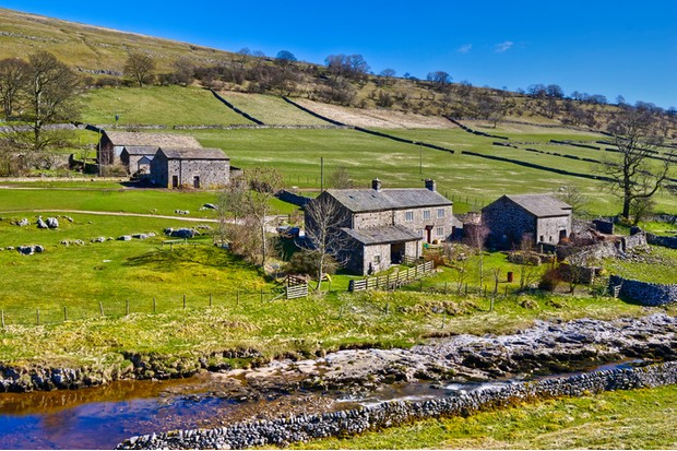 Scenic view of stone farm buildings in countryside with stream in foreground, Yockenthwaite, Wharfdale Valley, Yorkshire, England.