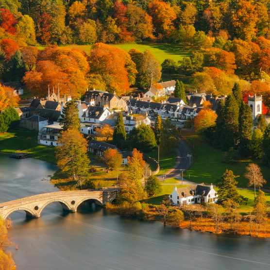 The village of Kenmore on the shores of Loch Tay viewed from Black Rock with the River Tay flowing beneath Kenmore Bridge surrounded by autumn colour.