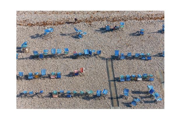 Deck chairs on beach, in the village of Beer, Devon, England, UK