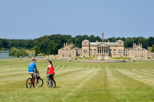 Couple on bikes taking in the view across sweeping lawns towards the grand 18th Century manor house on the Holkham Hall Estate, Holkham Hall Estate, Norfolk, England.