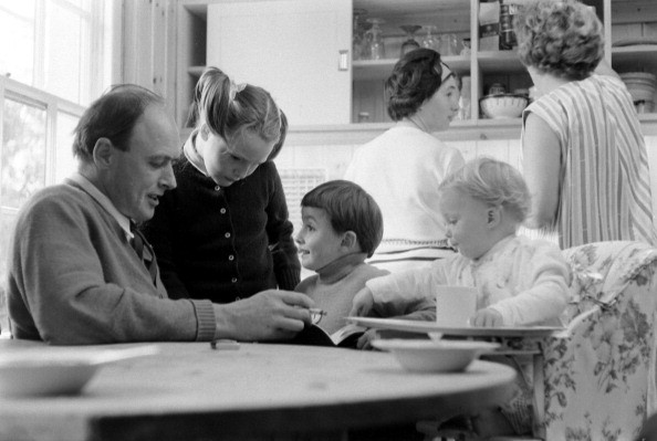 British author Roald Dahl (1916 - 1990) reads to three of his children, from left, Tessa, Theo, and Ophelia, in the kitchen of his home, Great Missenden, Buckinghamshire, England, September 1965. Teh two women in the background are unidentified. (Photo by Leonard McCombe/The LIFE Picture Collection/Getty Images)