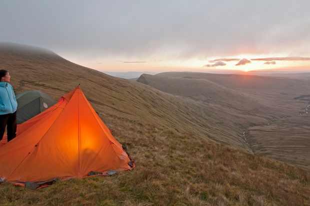 Hiker at campsite overlooking landscape