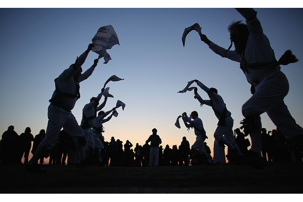 GLASTONBURY, ENGLAND - MAY 01:  Members of the Cam Valley Morris Men dance at a May Day dawn celebration in front of St. Michael's Tower on Glastonbury Tor on May 1, 2013 in Glastonbury, England. Although more synonymous with International Workers' Day, or Labour Day, May Day or Beltane is celebrated by druids and pagans as the beginning of summer and the chance to celebrate the coming of the season of warmth and light. Other traditional English May Day rites and celebrations include Morris dancing and the crowning of a May Queen with celebrations involving a Maypole.  (Photo by Matt Cardy/Getty Images)