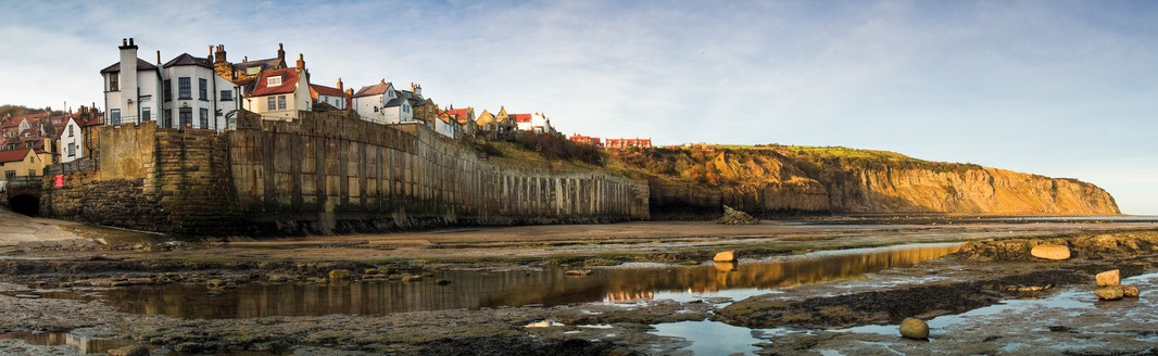 """A wide angle panoramic view of Robin Hood's Bay, North Yorkshire. The tiny fishermen's cottages of the old village snuggle along the steep, twisting street that leads down to the shore. The raging storms have taken their toll, claiming many buildings as the limestone cliffs erode. In 1780, 22 cottages fell into the sea, and in 1975, the 40 ft high sea-wall was completed to protect the picturesque village from further erosion. Whilst the beach is not suitable for bathing it is popular with fossil-hunters. Similar images:"""