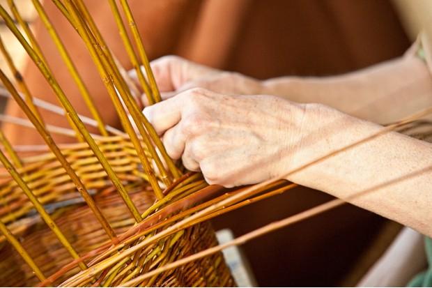 """Hands of a women, lacing a basket."""