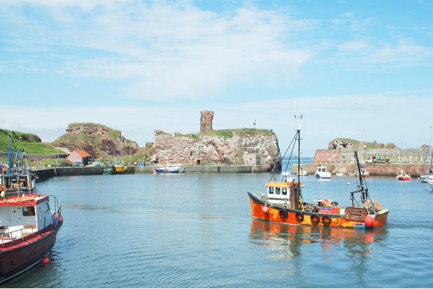 """dunbar harbour with castle ruins in background, fishing boats in foreground sunny day blue sky"""