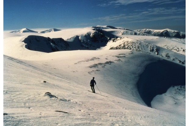 A lone skier surveys the surrounding peaks from Cairngorm Mountain, over 4000 feet in this popular ski-ing country