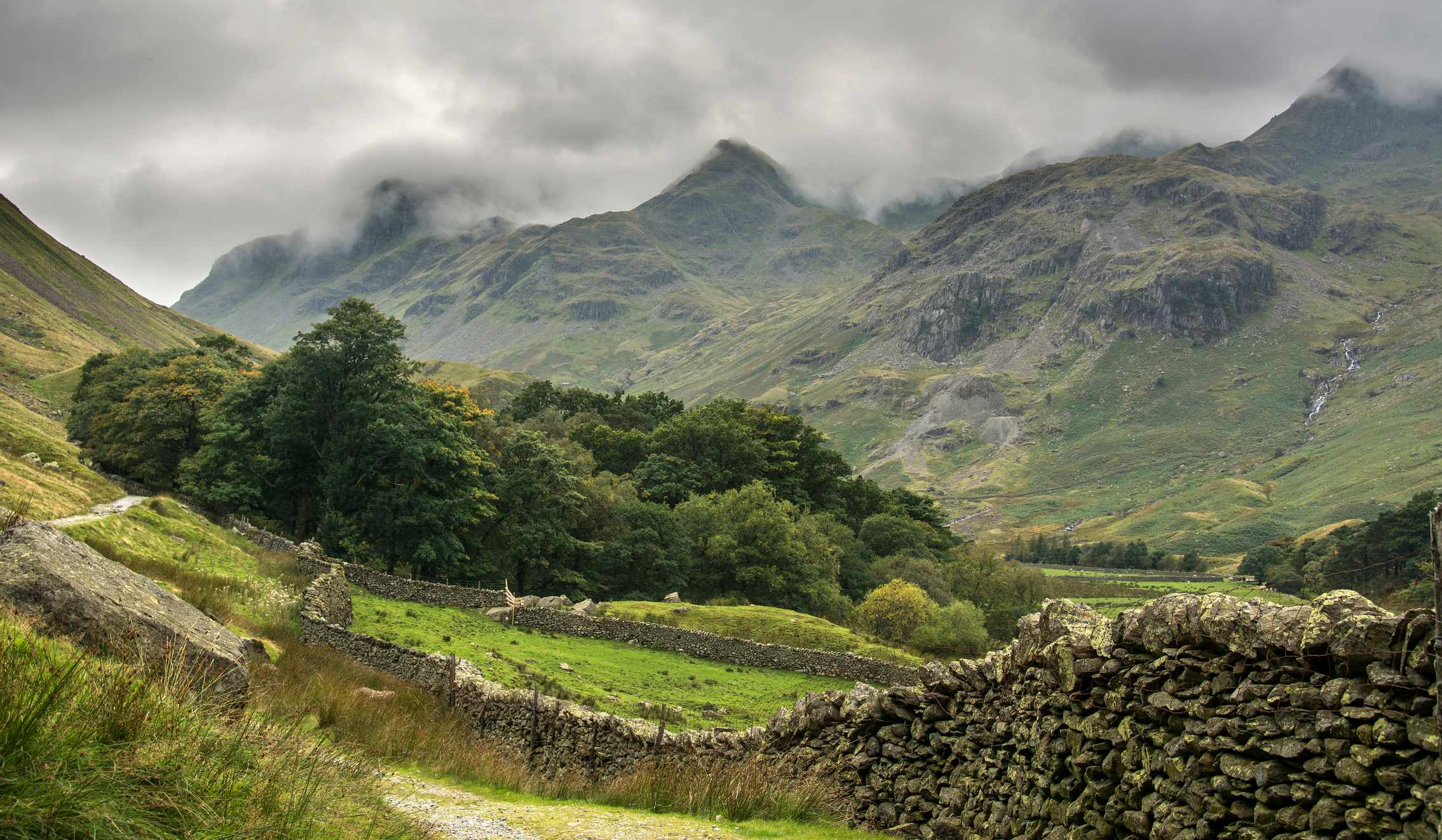 Valley in English Lake District with misty mountains and woodland.