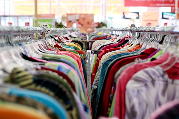 a variety of colorful shirts hang on a clothing rack at a thrift store