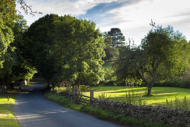 UNITED KINGDOM - SEPTEMBER 07: Country lane rural scene in Swinbrook in The Cotswolds, England, United Kingdom