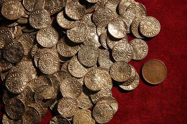 LONDON, ENGLAND - FEBRUARY 10:  A modern day one pence coin (R) is displayed with Anglo Saxon silver pennies at The British Museum on February 10, 2015 in London, England. Rare coins and other finds are being shown as the Treasure Annual Report 2012 is launched. Under the Treasure Act 1996 there is a legal obligation for finders to report what they find to the state. The silver Anglo Saxon coin hoard containing around 5,200 items was discovered in Lenborough, England in December 2014.  (Photo by Peter Macdiarmid/Getty Images)