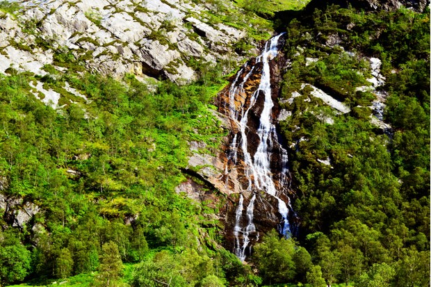 A rocky landscape of lush summer greenery on either side of Steall Waterfall. Taken in the month of June near Ben Nevis and Fort William in the Scottish Highlands