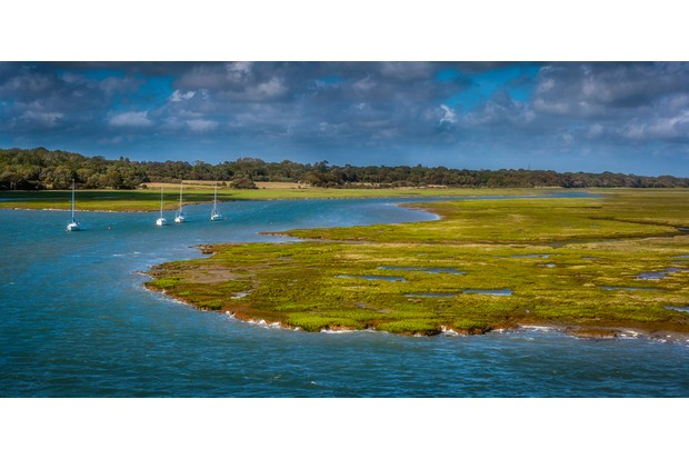 A stunning image of the Lymington Marshes and entrance to the harbour, set against the backdrop of a stormy sky